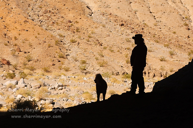 Man and his dog exploring a cave in Cottonwood Canyon, Death Valley National Park, California
