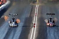 Feb. 23, 2013; Chandler, AZ, USA; NHRA top fuel dragster driver Antron Brown (left) races alongside David Grubnic during qualifying for the Arizona Nationals at Firebird International Raceway. Mandatory Credit: Mark J. Rebilas-