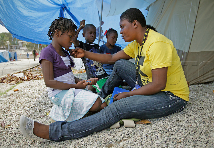 At a tent city in Dadadou Community Park in Delmas III area, International Rescue Committee case worker Aliene Cadet  interviews Gesula, 13, on March 2, 2010, to determine if she needs assistance. In Haiti it's a long drawn out process to start reuniting kids separated from their loved ones. Case workers with the International  Rescue Committee interview kids everywhere from tent cities to destroyed homes. .