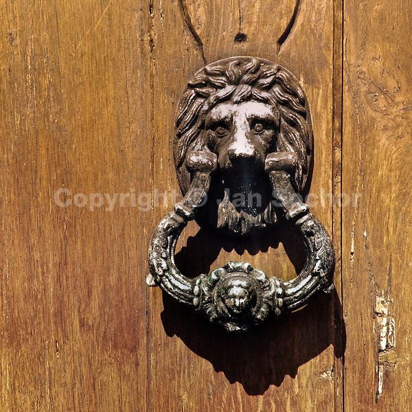 An Antique Door Knocker Is Seen Hung On The Wooden Door Of A Spanish  Colonial House