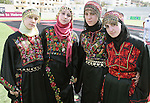Palestinian women who made the traditional Palestinian dress during a showing of it as it will be to create the largest traditional Palestinian dress in an attempt to enter the Guinness World Records at Al-Hussein stadium in the West Bank city of Hebron on October 25, 2009. the largest traditional Palestinian dress include knitted olive tress, Falastin (Palestinian), Palestinian flag and the word 'Al-Quds' (Jerusalem). Photo by Najeh Hashlamoun