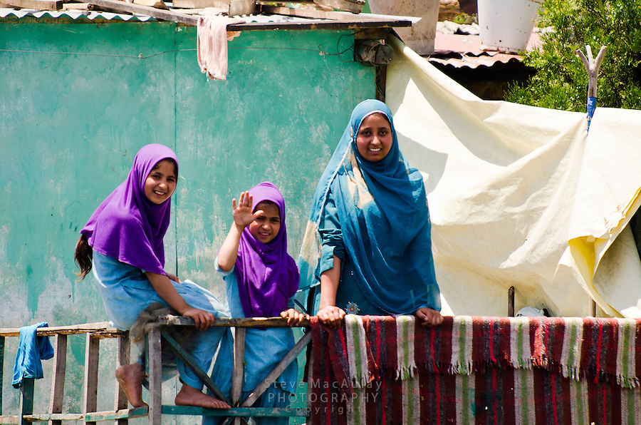 Smiling Muslim woman and children in colorful headscarves, Dal Lake, Srinagar, Kashmir, India.
