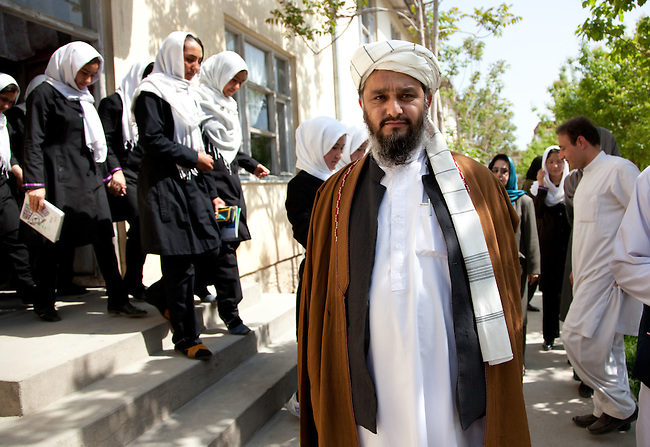 """03 May 2012, Kabul Afghanistan:  Students pass by Mullah Aziz Ullah, a local religious leader, at Sorya High School in West Kabul that benefits from the Education Quality Improvement Program (EQIP).  The Mullah has three daughters who all attend school along with his two sons. """" I want the best for all of my children not just the boys"""" says Mullah Aziz..EQIP is a program designed to increase equitable access to quality basic education, especially for girls, through school grants teacher training and strengthened institutional capacity with support from communities and private providers. Program interventions are primarily targeted toward general education, teacher training and curriculum development. The program is being implemented by the Afghan Ministry of Education. Picture by Graham Crouch/World Bank"""