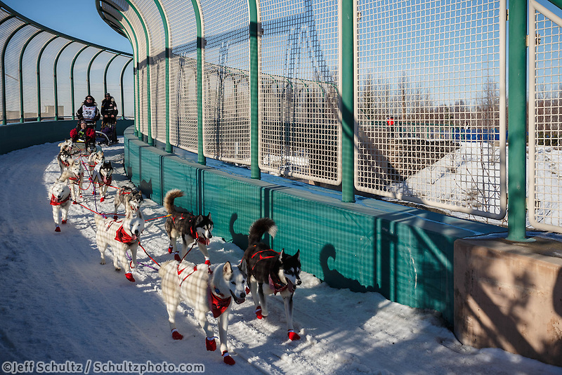 Veteran musher, Karen Ramstead, drives her dogs along the Tudor Road bridge during the ceremonial start to Iditarod 2014  in Anchorage, Alaska.<br /> <br /> Iditarod Sled Dog Race 2014<br /> PHOTO (c) BY JEFF SCHULTZ/IditarodPhotos.com -- REPRODUCTION PROHIBITED WITHOUT PERMISSION