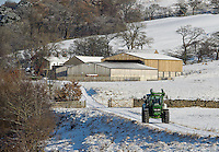 John Deere tractor traveling down a farm track in snow, Whitewell, Lancashire