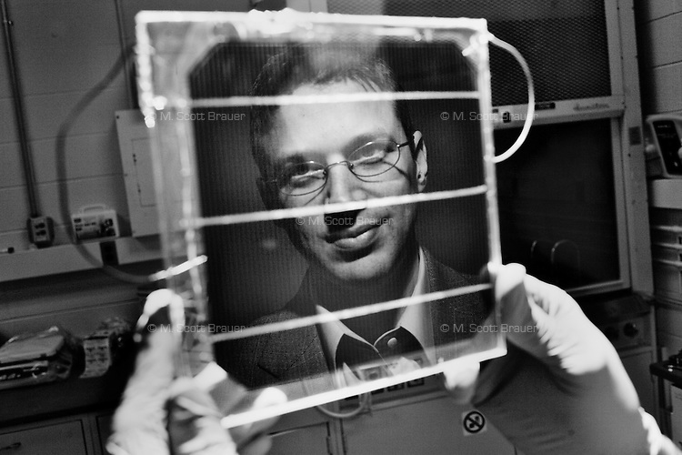 Reflected in a small solar cell, Dr. Jeffrey C. Grossman, a newly-tenured professor in the Materials Science and Engineering Department, poses for a picture in his lab at MIT in Cambridge, Massachusetts, USA.  Grossman's recent work focuses on three dimensional photovoltaics which are designed to optimize the efficiency of solar energy collection.