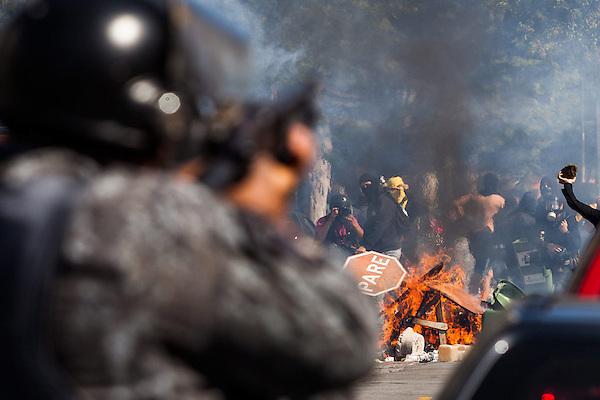 BRA19. SAO PAULO (BRASIL), 12/06/2014.- Un grupo de manifestantes se enfrenta a miembros de la Policía brasileña hoy, jueves 12 de junio de 2014, durante la primera protesta contra el Mundial de fútbol Brasil 2014 registrada en Sao Paulo (Brasil), en el día en que comienza la competición. Cerca de 150 hombres de la Tropa de Choque de la Policía Militarizada del estado de Sao Paulo dispersaron a un grupo de 50 manifestantes que intentaba marchar por la avenida Radial Este, la principal vía de acceso al Arena Corinthians, el estadio de Sao Paulo en que se disputará el partido inaugural del Mundial. EFE/Marcos Méndez
