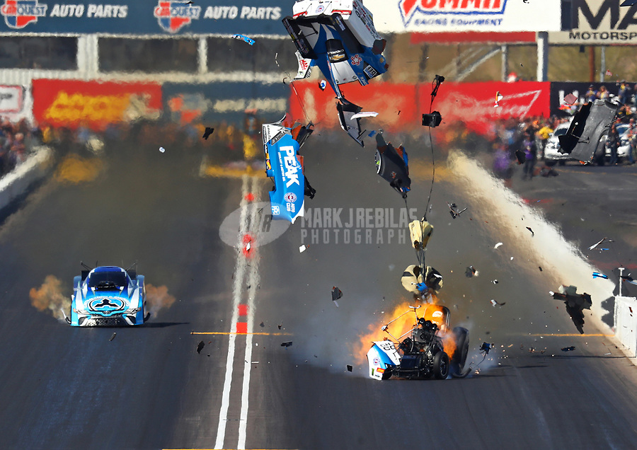 Feb 25, 2018; Chandler, AZ, USA; NHRA funny car driver John Force (right) explodes the body off his car on fire alongside Jonnie Lindberg during the Arizona Nationals at Wild Horse Pass Motorsports Park. Mandatory Credit: Mark J. Rebilas-USA TODAY Sports