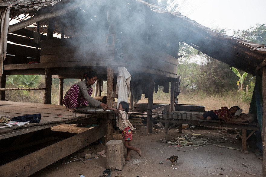 """Cambodia - Kampong Speu Province - Louv Veoun, 39, preparing rice, the only meal her family has once per day, under the broken roof of her wooden house next to her two daughters. """"I don't want money, I want my old land back. It is the land of my ancestors"""". Louv Veoun, 39 and mother of 8, was living in a small cottage on her rice field in Kork until March 2010, when she was dispossesed of her two hectares of land and compensated with 25 USD. She was forced to abandon her house and settle in a piece of land belonging to some of her relatives, close to the plantation. Today, she lives in utter poverty together with her family."""