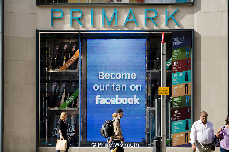 Become our fan on Facebook.  Message on a screen in a Primark store window, Oxford Street, London.