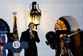 United States President Barack Obama prepares to look through a telescope with the help of Agatha Sofia Alvarez-Bareiro after delivering remarks at the second White House Astronomy Night attended by students, teachers, scientists, astronauts and others in the South Lawn of the White House in Washington, DC. <br /> Credit: Aude Guerrucci / Pool via CNP
