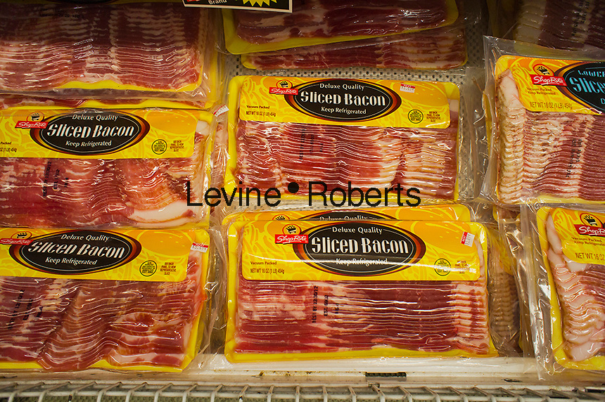 "Packages of house brand bacon are seen in a supermarket cooler in New York on Saturday, October 6, 2012. Agricultural economists are calling a shortage of bacon ""hogwash"" but prices may rise up to 10 percent. Feed costs due to the recent drought caused famers to bring their herds to market earlier resulting in a shortage and higher prices later on.  (© Richard B. Levine)"