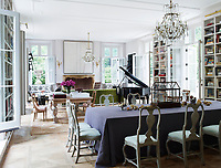 In the family room, the 18th-century chairs around the dining table are Swedish, the 19th-century gilt bronze-and-crystal chandeliers are French, the piano is a 1914 Steinway and the wall sculptures are by Louise Nevelson. The ceilings throughout are painted in Farrow & Ball's All White.
