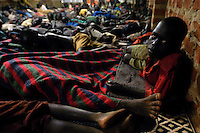 Okello Charles, 10, joins about 200 other children under the roof of shelter constructed by Catholic Relief Services in the Rural Focus Uganda center for night commuters (RUFOU) in Gulu, Uganda, March 24, 2004. The shelter is one of many housing night commuters in the war-torn northern Uganda region.  Night commmuters leave their homes in the countryside before nightfall to avoid bands of the Lord's Resistance Army who abduct people, especially children to carry heavy loads and to become soldiers in their self-proclaimed rebel army.  Okello is the oldest of five who walk three kilometers to the center every night. The center has three buildings and four tents which house about 1,200 children each night.(Rick D'Elia)