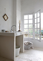 The bathroom is rudimentarily furnished and has French windows that lead out to the patio
