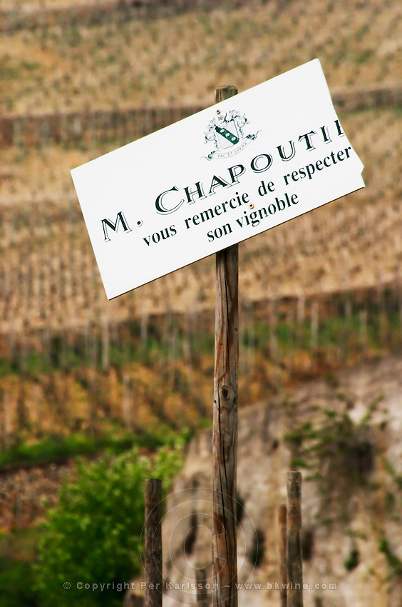 A broken sign in the vineyard saying M Chapoutier thanks you for respecting his vineyards. The Hermitage vineyards on the hill behind the city Tain-l'Hermitage, on the steep sloping hill, stone terraced. Sometimes spelled Ermitage. Tain l'Hermitage, Drome, Drôme, France, Europe