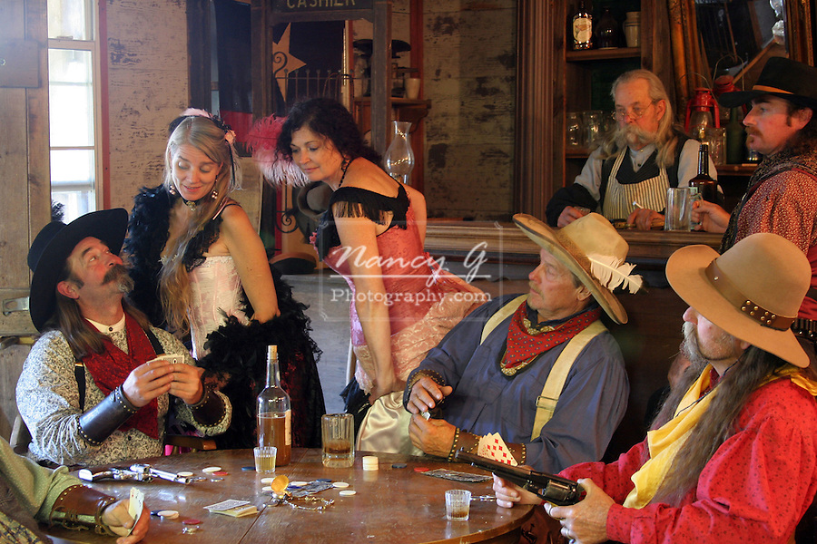 Saloon girls looking at a cowboys hand of cards who is playing Poker in the bar