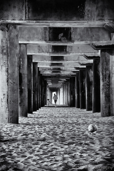 Man and daughter walking underneath a pier.  Taken with infrared camera