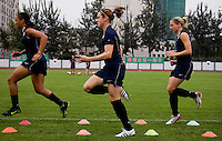 USWNT midfielders Angela Hucles, Heather O'Reilly, and Lindsay Tarpley run through a set of cones during practice at Beijing Normal University for the upcoming semi-final game against Japan in the 2008 Beijing Olympics in Beijing, China.