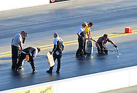 Apr. 13, 2012; Concord, NC, USA: NHRA officials work to patch the track during qualifying for the Four Wide Nationals at zMax Dragway. Mandatory Credit: Mark J. Rebilas-
