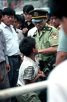 A beggar is arrested by a policeman at the railway station in Guangzhou.