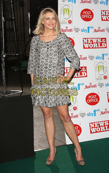 ALI BASTIAN.Children's Champions Awards 2009 at the Grosvenor House Hotel, Park Lane, London, England, March 4th 2009..full length black and white print tiered ruffle dress long sleeved hand on hip Christian Louboutin grey gray peep toe platform shoes heels buttons .CAP/ROS.©Steve Ross/Capital Pictures
