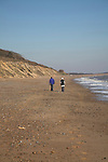 Two people walking on beach. Dunwich beach and cliffs, North Sea coast, Suffolk, East Anglia, England