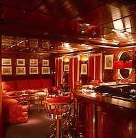 A luxurios saloon bar with rich wood panelling and red leather upholstery