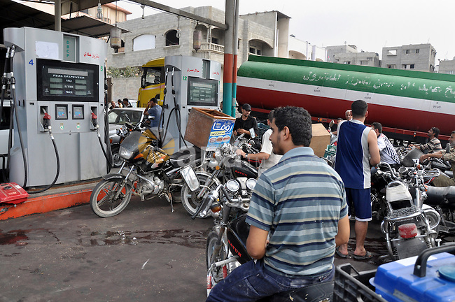 Palestinians wait to fill containers with fuel from a petrol station in Gaza city on Sep 01, 2013. Fuel stations in the Gaza Strip free of fuel due to the crisis in Egypt and the restricting of the fuel lines through the 'smuggling tunnels' between Rafah and the Egyptian side of the border. Photo by Mohammed Talatene