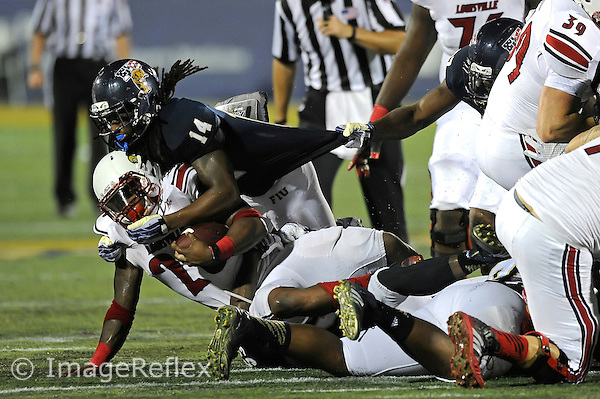20 September 2014:  FIU safety Demarkus Perkins (14) tackles Louisville running back Brandon Radcliff (23) in the second half as the University of Louisville Cardinals defeated the FIU Golden Panthers, 34-3, at FIU Stadium in Miami, Florida.