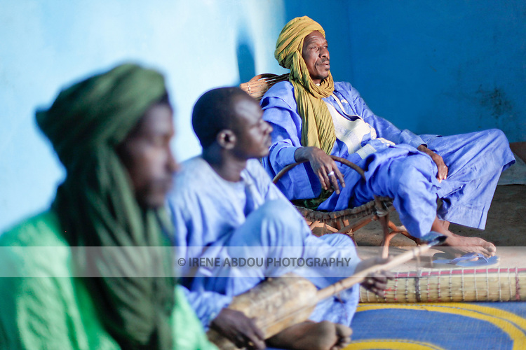 In Muslim West Africa, during the days leading up to Tabaski (Eid-Al-Adha), the griot's work grows.  Visiting families throughout the town, griots recite family histories through poetry, song, and music, refusing to leave the compound until the family pays them for their troubles.  Here, two griots, one playing a traditional guitar, call on a Fulani family in Djibo in northern Burkina Faso.  The third man in green - their assistant - is responsible for keeping an eye on the area and letting the griots know when a family member returns after a long absence.