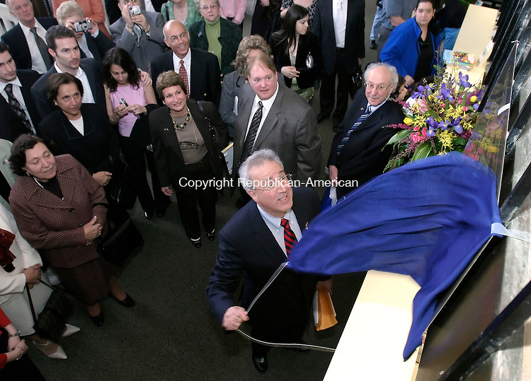 WATERBURY, CT, 01 April 2006- 040106BZ01- Elias Aburdene, on behalf of the Aburdene Family, unveils a plaque dedicating the lobby of the Silas Bronson Library in memory of his parents Felix and Olga Aburdene during Aburdene Family Day festivities at the library Saturday.<br />  Jamison C. Bazinet Republican-American