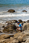 young photographer with tripod mounted camera shooting tidal scene