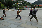 Tai Chi class exercising in public space in city centre, Bergen, Norway