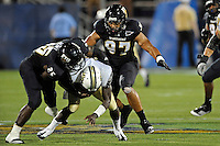 17 September 2011:  FIU linebacker Jordan Hunt (25) and defensive end Tourek Williams (97) combine to bring down UCF quarterback Jeff Godfrey (2) in the second half as the FIU Golden Panthers defeated the University of Central Florida Golden Knights, 17-10, at FIU Stadium in Miami, Florida.