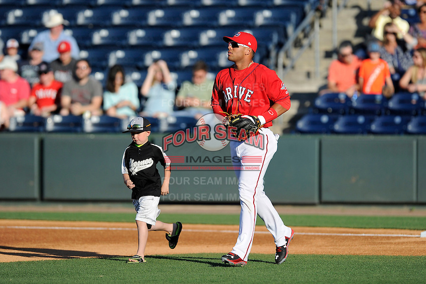 Second baseman Yoan Moncada (24) of the Greenville Drive runs onto the field with a youth ballplayer in a game against the Charleston RiverDogs on Saturday, May 23, 2015, at Fluor Field at the West End in Greenville, South Carolina. The Cuban-born 19-year-old Red Sox signee has been ranked the No. 1 international prospect in baseball by Baseball America. Charleston won 5-4. (Tom Priddy/Four Seam Images)