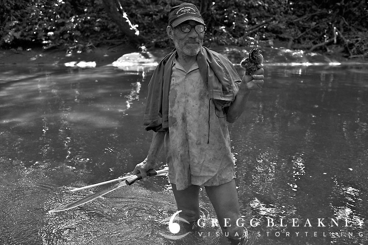 Hunter along a small river tributary displays his prize catch - Pacific Coast - Colombia