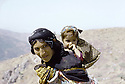 Irak 1985.Dans les zones libérées, région de Lolan, une femme sur la piste avec son enfant sur le dos.Iraq 1985.In liberated areas, Lolan district, a womn and her child on  the track