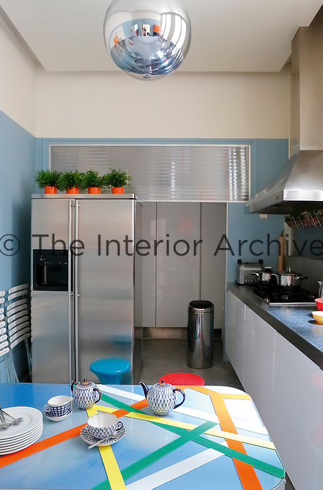 The table in the contemporary kitchen has been customised by Sacha with lengths of colourful sticky tape
