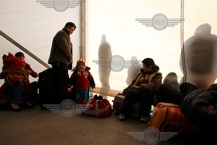 Migrant workers wait for their train to be called at the railway station in Shanghai.