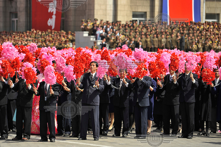 Participants during a ceremony marking the 100th birthday of Kim Il-sung wave pink and red fake flowers as part of the parade on Kim Il-sung Square.