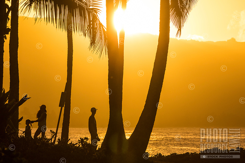 A family of three enjoy sunset at Hale'iwa Ali'i Beach Park, North Shore, O'ahu.