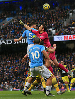 2nd November 2019; Etihad Stadium, Manchester, Lancashire, England; English Premier League Football, Manchester City versus Southampton; Alex McCarthy of Southampton punches the ball clear challenged by John Stones of Manchester City - Strictly Editorial Use Only. No use with unauthorized audio, video, data, fixture lists, club/league logos or 'live' services. Online in-match use limited to 120 images, no video emulation. No use in betting, games or single club/league/player publications