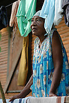 An elderly, Mayan woman framed by  drying laundry looks out from her porch in the Garifuna village of Barranco in southern Belize.