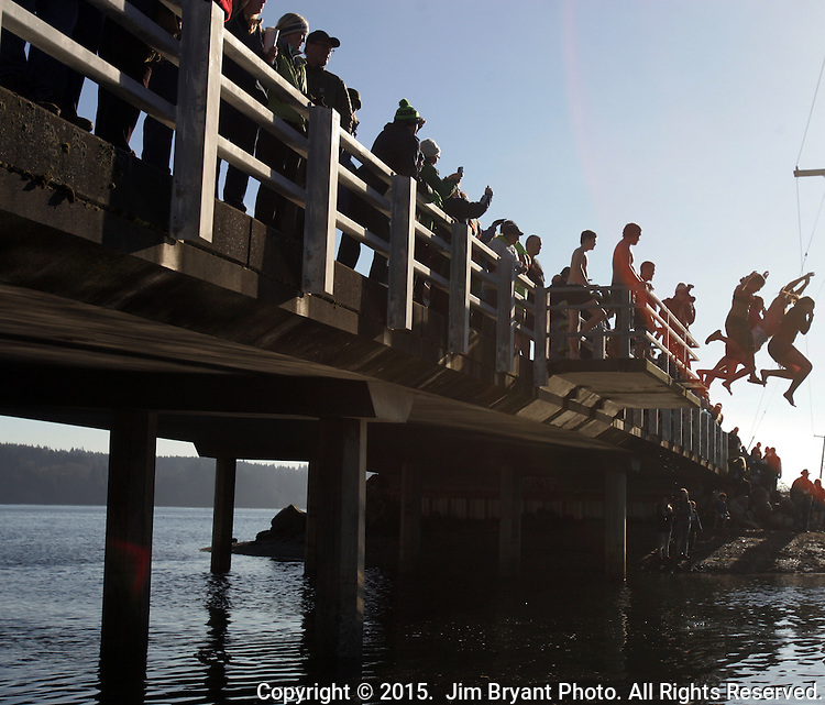 Participants leap off the bridge into the Burley Lagoon during the 31st annual Polar Bear on January 1, 2015 in Olalla, Washington. Over 500 hardy participants joined in on the annual New Year's Day Tradition by jumping into the chilly lagoon waters during the annual Polar Bear Plunge.  ©2015.  Jim Bryant Photo. All Rights Reserved.
