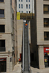 Man ascending escalator in city centre of Lleida, Cataluna, Spain.