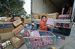 "Laura Rodriguez helps unload supplies at the Holding Institute in Laredo, Texas, on March 3, 2017. The clothing, food and other materials were donated by Cuban-Americans in other parts of the country and shipped by truck to Laredo for distribution to hundreds of Cuban immigrants stuck on the other side of the Mexican border, caught in limbo by the elimination in January of the infamous ""wet foot, dry foot"" policy of the United States. They are not allowed to enter the U.S. yet most don't want to return to Cuba. Many churches in Nuevo Laredo, Mexico, have become temporary shelters for the immigrants, and congregations there rotate responsibility for feeding the Cubans. Such solidarity from ordinary Mexicans will be tested in coming months, as not only are the Cubans stuck at the border, but the U.S. has stepped up deportations of Mexican nationals, while at the same time detaining many undocumented workers from other nations and simply dumping them on the US-Mexico border. Rodriguez is a volunteer with Holding, an institution sponsored by United Methodist Women."