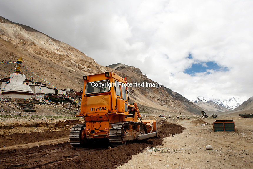 China started building a controversial 67-mile &quot;paved highway fenced with undulating guardrails&quot; to Mount Qomolangma, known in the west as Mount Everest, to help facilitate next year's Olympic Games torch relay./// A bulldozer in front of Rongbuk Monastery near Everest Base Camp.<br /> Tibet, China<br /> July, 2007