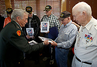 NWA Democrat-Gazette/DAVID GOTTSCHALK   Captain Clifford Mosier (from left), retired Army, hands out a book titled Korea Reborn A Grateful Nation Monday, May 1, 2017, to Max Page, Lehman Turner, Vernon Hammock and Jim Oden, all Korean War veterans, in Fayetteville. The four were part of a group of nine Korean War veterans that were recognized by the Northwest Arkansas Chapter of Military Officers Association of America Monday and received the book. The books were published by the South Korean government in gratitude of the United States military service in the war and documents the growth and progress that country has sustained over the past 60 years.