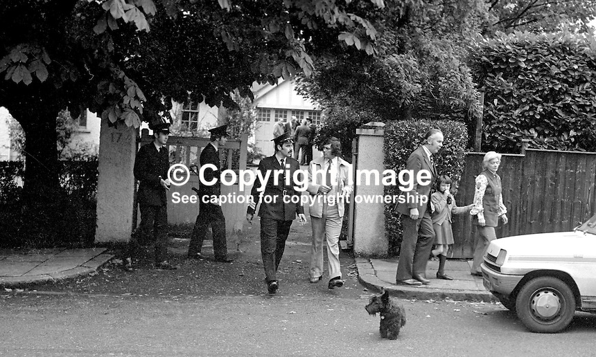 Deirdre Conaghan, the nine year old daughter of Roman Catholic Judge Rory Conaghan, and a witnesss to her father's murder at Beechlands, Belfast, N Ireland, is escorted away from her family home by Liam McCollum, QC, a prominent member of the local legal profession. On the same day at a approximately the same time a Protestant magistrate, Martin McBurney, was also murdered. A subsequent Provisional IRA statement said they had been assassinated for &quot;collaborating with the British war machine&quot;. 197409160494d.<br />